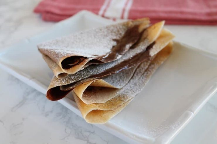 Stacked Keto Crepes with powdered sugar on a white plate