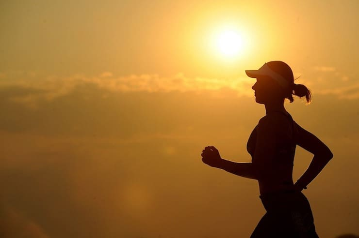 Silhouette of woman running with sunset in background