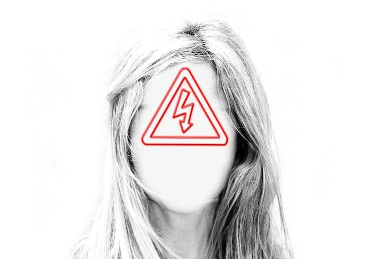 Woman with white out face and red warning sign triangle over face