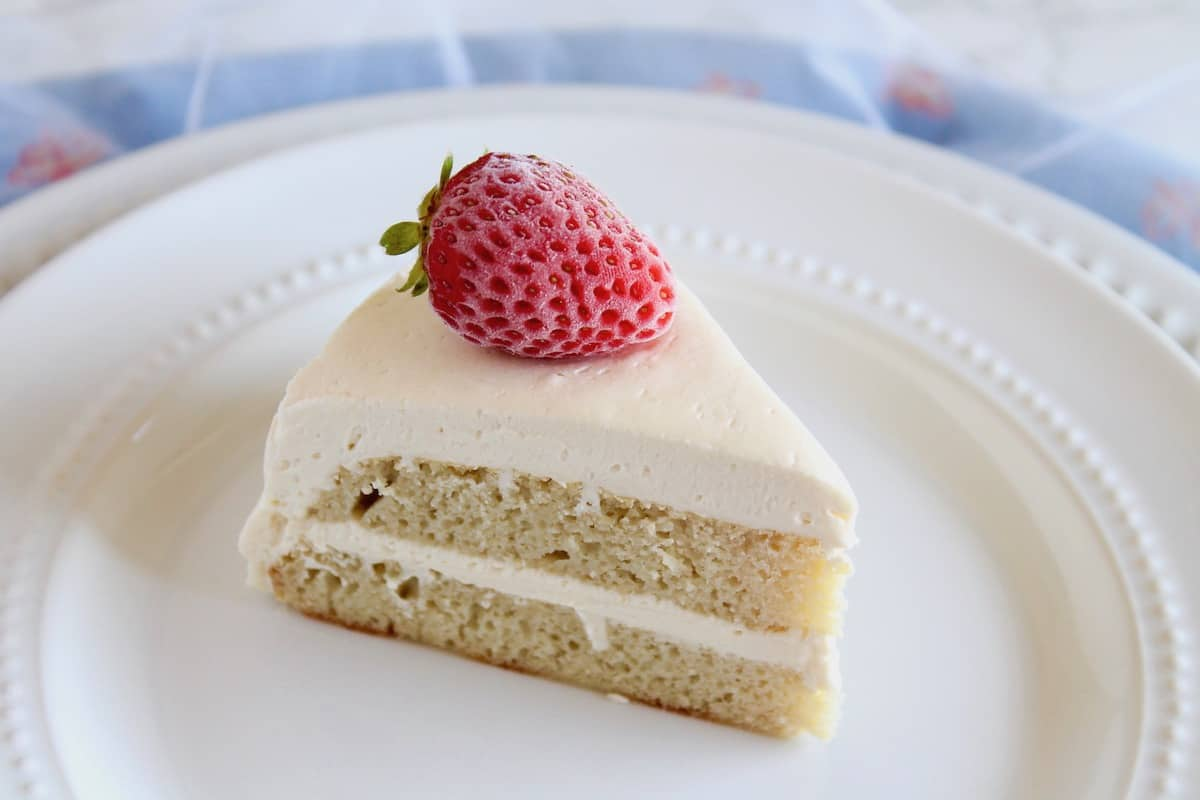 Slice of white frosted coconut flour layer cake on white plate with strawberry on top next to blue cloth