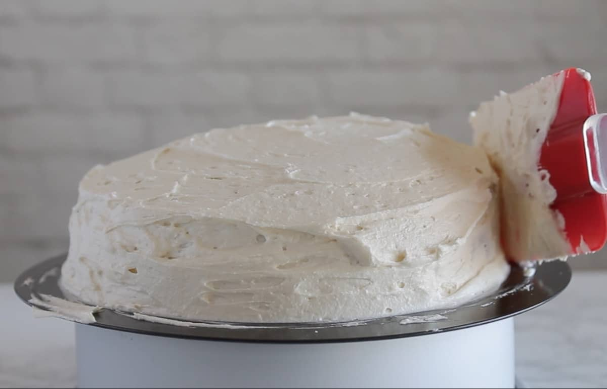 white frosted coconut flour cake being frosted with a red spatula