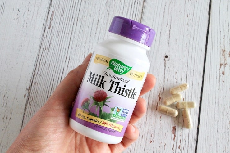 Hand holding bottle of milk thistle with tan capsules in background on white wooden table