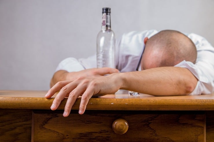 Man with head down on desk holding a bottle of alcohol