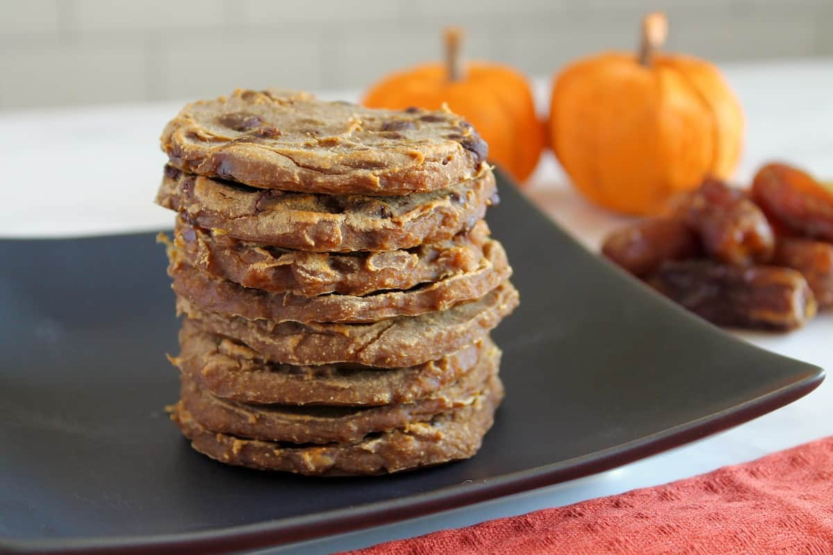 Stack of banana pumpkin cookies on black plate with pumpkins and dates in background