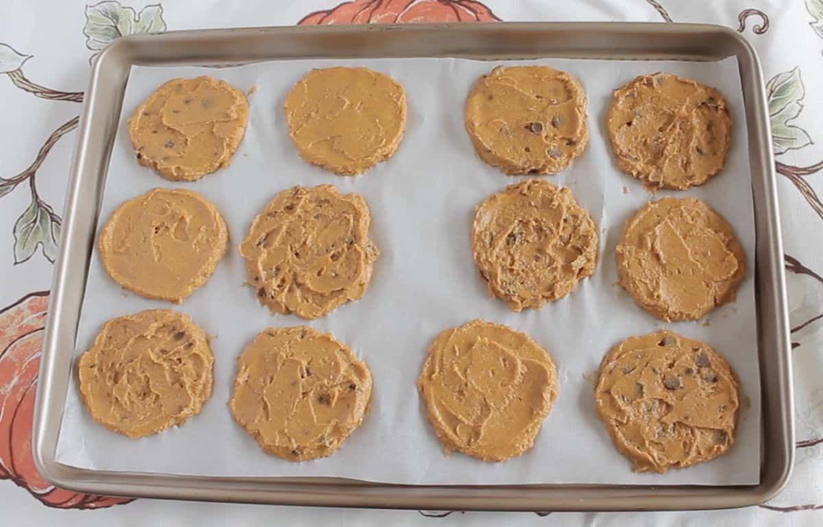 Overhead view of uncooked flattened banana pumpkin cookie dough on baking sheet