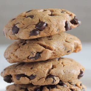 close up of four keto chocolate chip cookies stacked on a white plate with white background