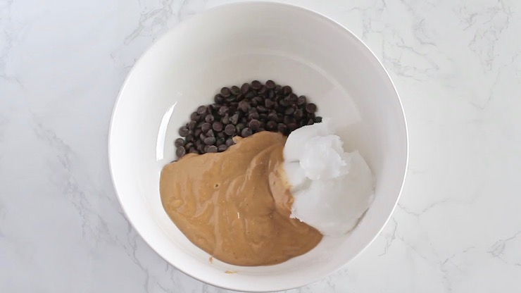 Keto fudge ingredients including chocolate chips, cashew butter and coconut oil in a white bowl