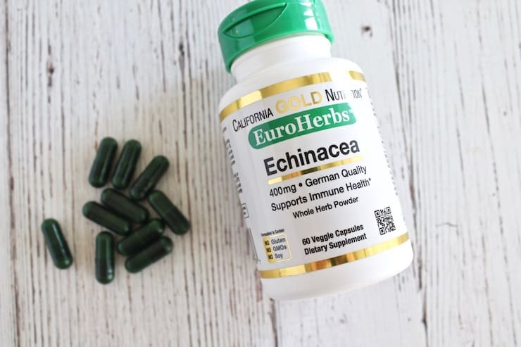 Bottle of echinacea laying flat on white wooden table with green supplement capsules next to it
