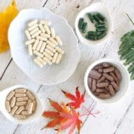 Overhead view of different colored supplement capsules in white trays with colorful plants around it