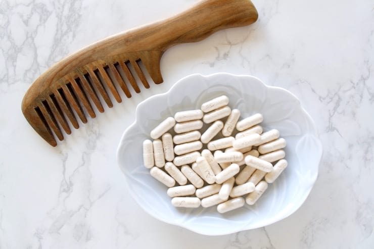 Light blue dish with white capsules in it on a white marble surface next to a wooden comb