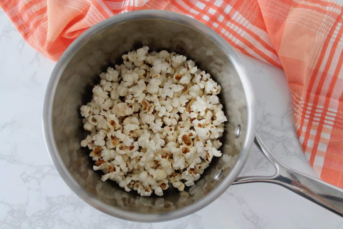 Stainless steel pot with popped popcorn in it on a white marble surface next to a red and white plaid dish cloth