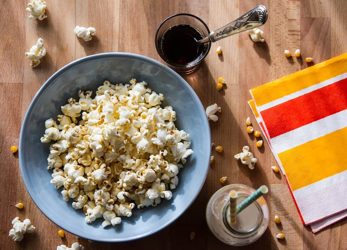 Overhead view of popcorn in a large grey bowl with drinks beside it