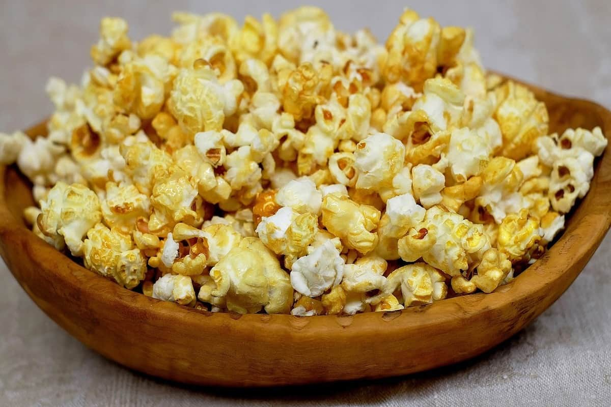 Popcorn in a wooden bowl on a grey surface