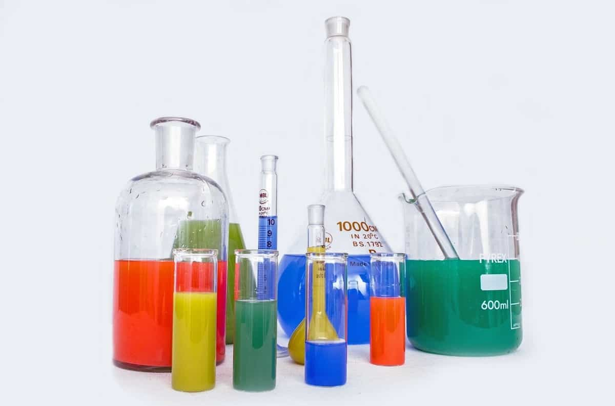 Different sized beakers with various colored liquids in them on a white table