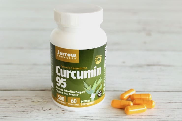 Supplement bottle of curcumin next to loose orange capsules on a white wooden surface