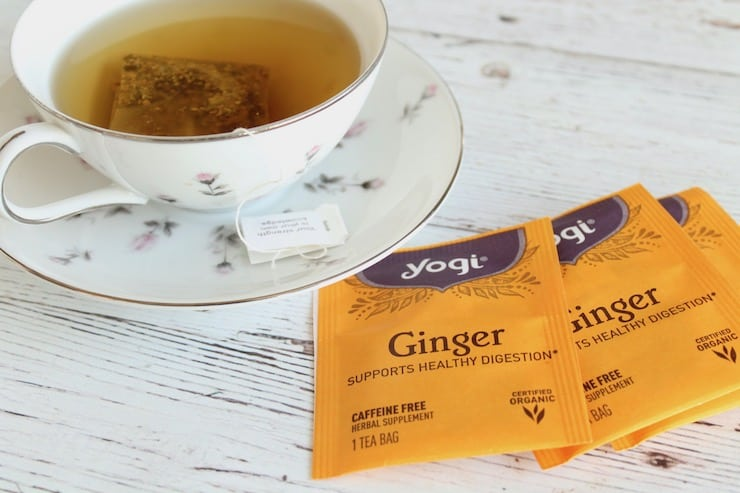 Individually wrapped ginger tea bags next to a tea cup and saucer with tea in it