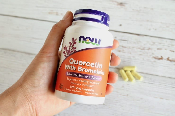 Hand holding a supplement bottle of quercetin with bromelain over a white wooden surface