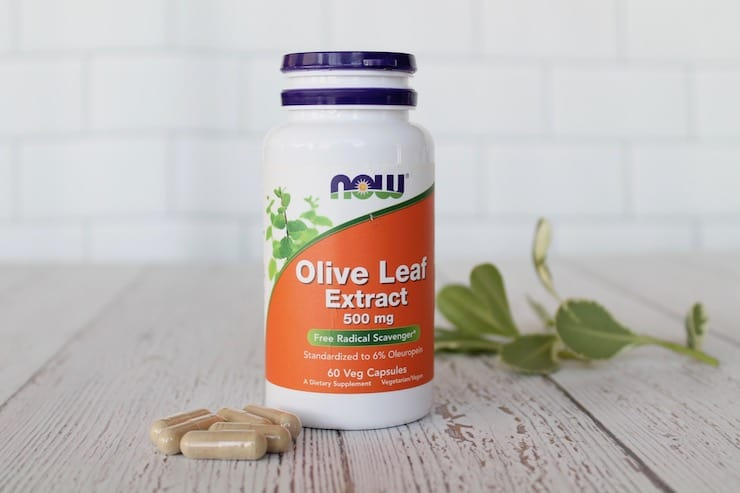 Supplement bottle of olive leaf extract next to loose capsules on a white wooden surface