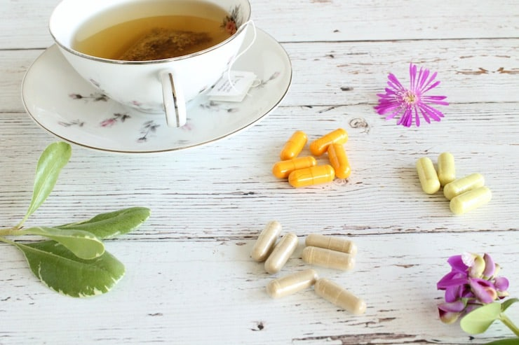 Loose different colored capsules on a white wooden surface next to flowers and a cup of tea on a saucer