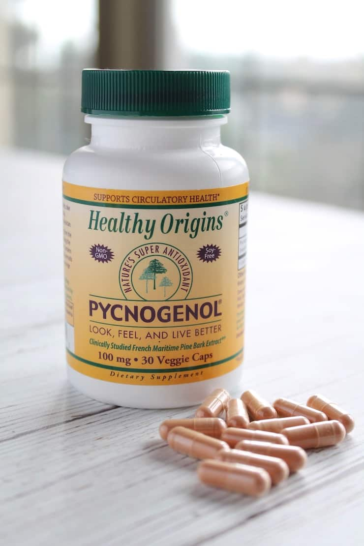 Bottle of pycnogenol supplement with red capsules next it on a white wooden surface