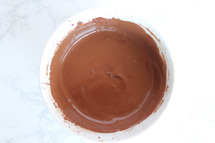 Chocolate keto mug cake mixed batter in a white bowl on a white marble surface