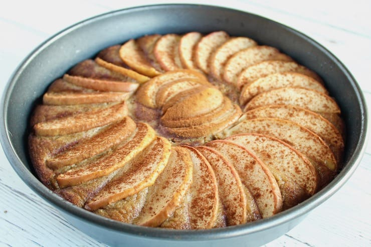 Whole baked apple cake in cake pan on a white wooden table