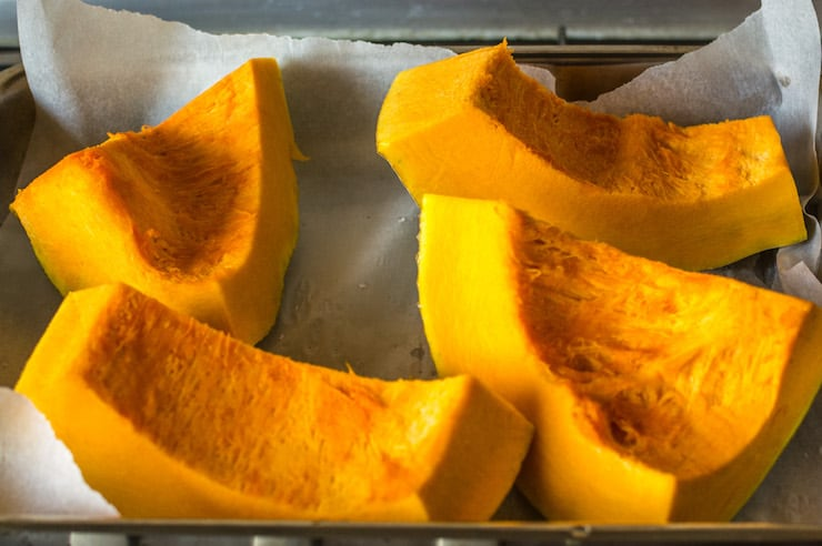 Large chunks of pumpkin on a baking sheet lined with parchment paper