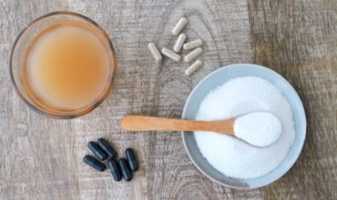 Plate of white powder with a wooden spoon in it next to black and brown supplement capsules and a glass of light brown liquid on a wooden table