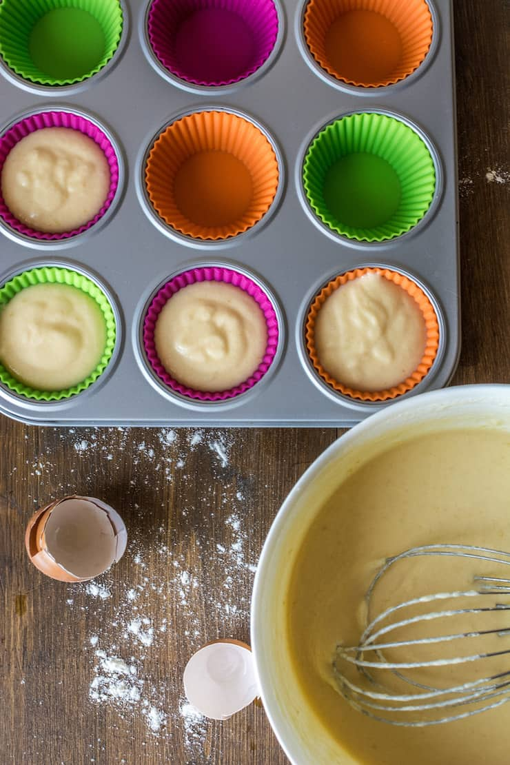Overhead view of white bowl of cupcake batter with whisk in it next to muffin tin lines with muffin liners with batter in the liners