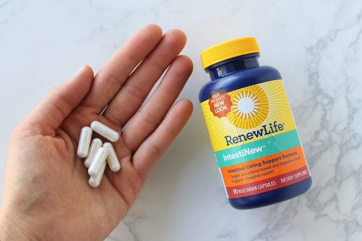A bottle of intestinew supplements laying flat on a white marble surface with a hand holding white capsules next to it
