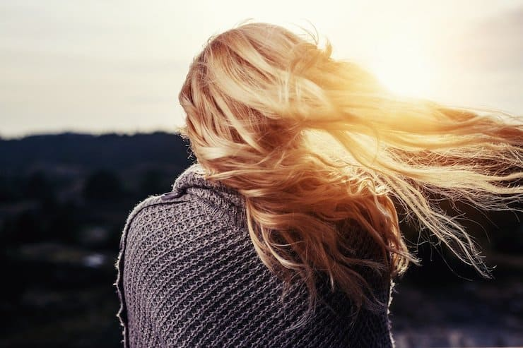 Backside view of a woman's head with her blonde hair blowing in the wind with the sun shinning through