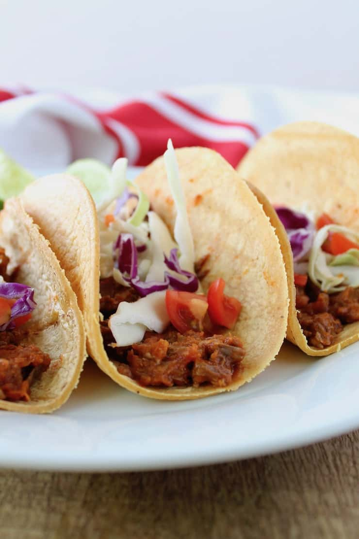 three shredded beef tacos on a white plate on a wooden table with a red and white dish towel in the background