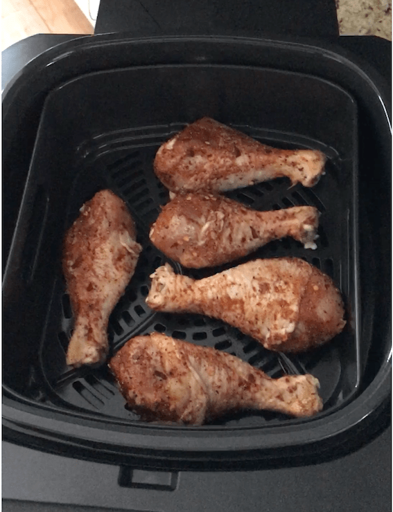 Partially cooked spiced chicken drumsticks in air fryer basket