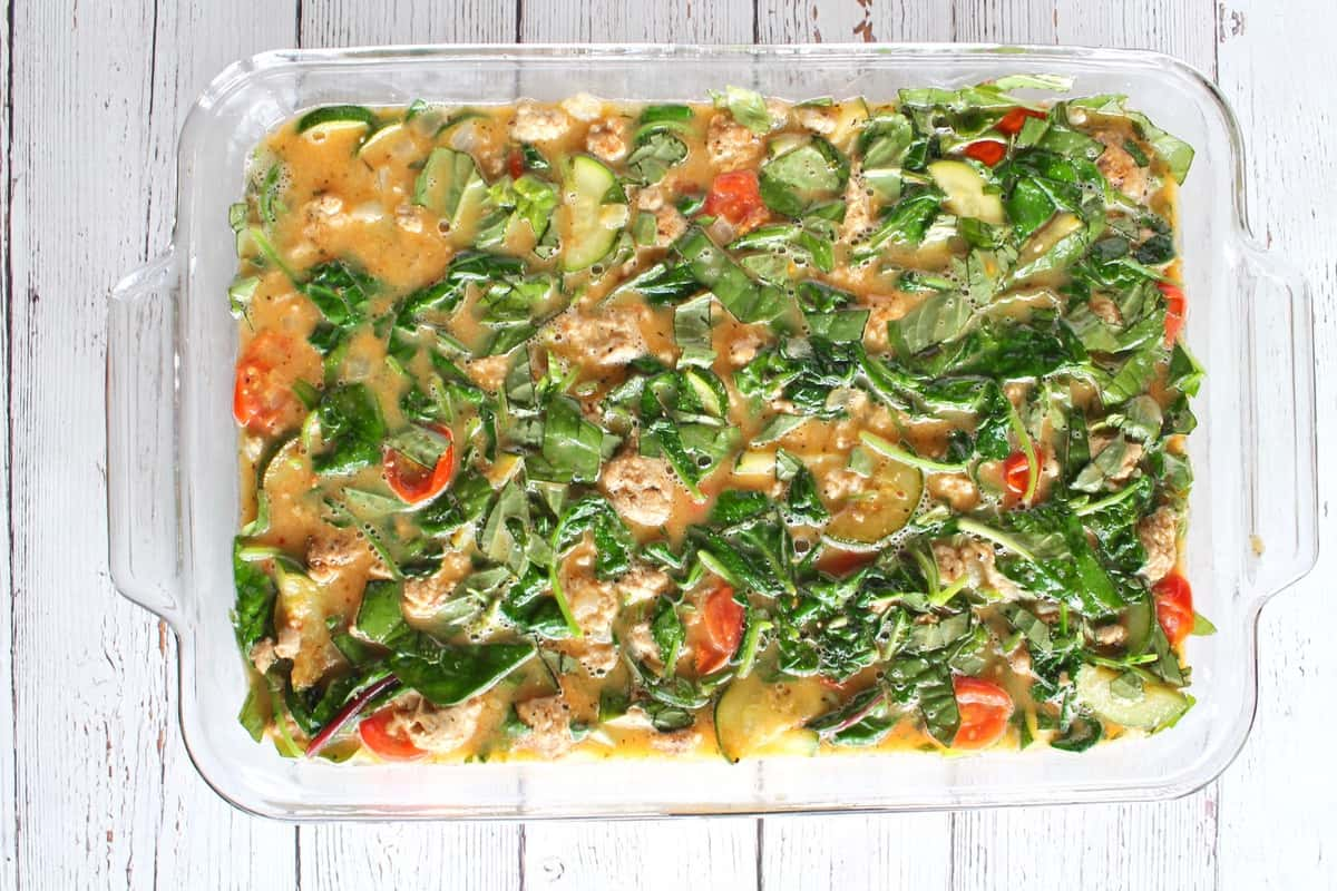 uncooked turkey and veggie baked frittata in a clear rectangular baking dish on white wooden surface