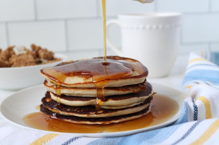 Close up of stacked pancakes with maple syrup being poured over them on a white plate with a blue, white and yellow striped kitchen towel next to it with a white bowl filled with granola and a white mug in the background on a white marble surface