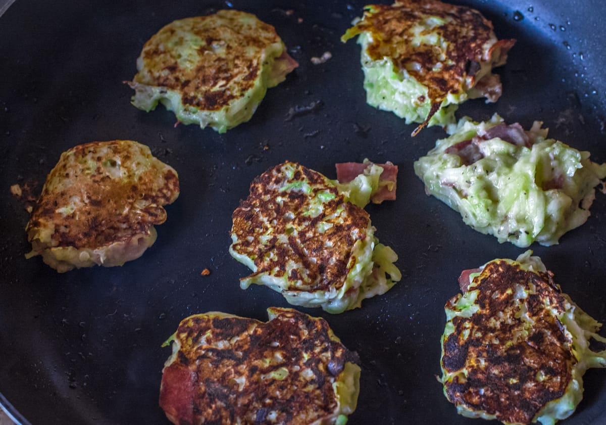 gluten free zucchini fritters cooking on a black cast iron skillet