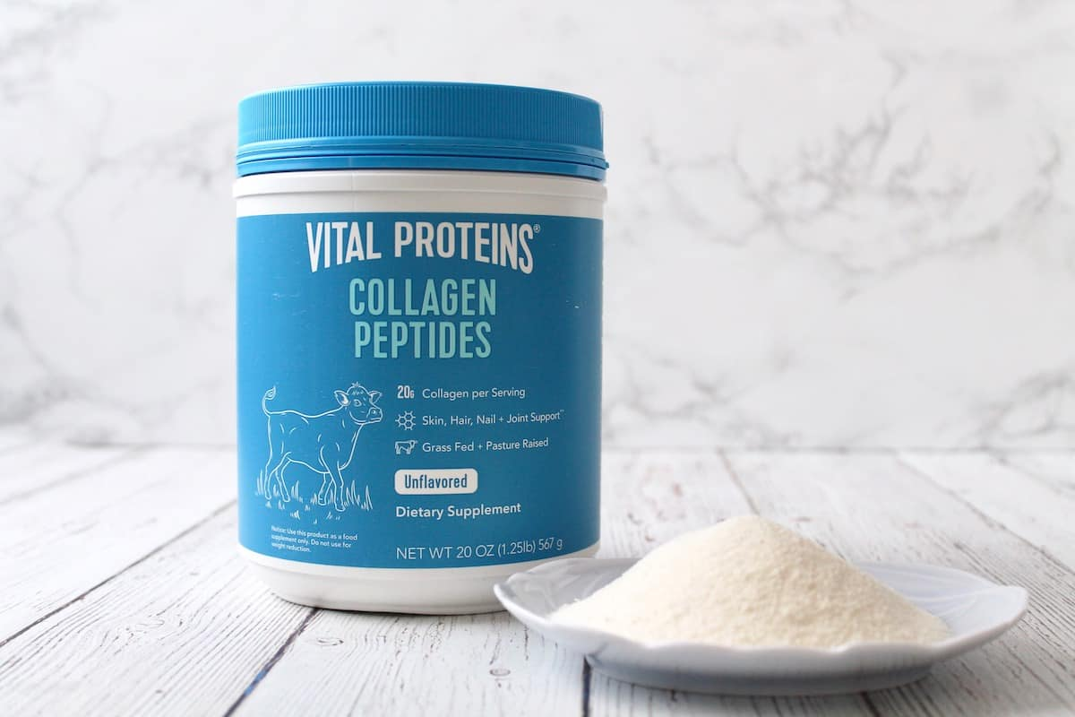 Blue tub of vital proteins collagen peptides next to dish with white powder in it on a white wooden surface with marble background