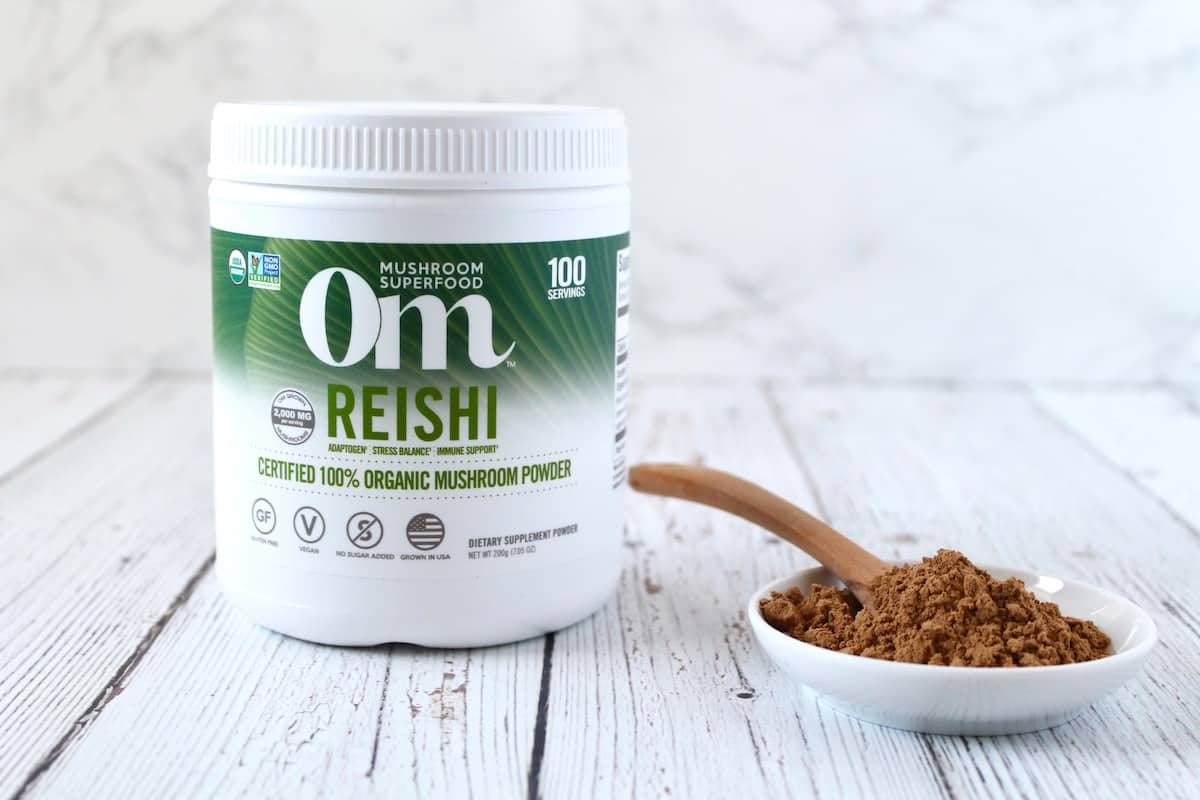 White tub of Om reishi mushroom powder next to a small white dish of brown powder with a wooden spoon in it on a white wooden surface with a white marble background