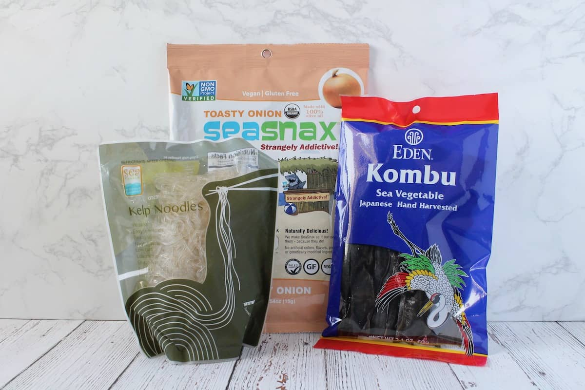 One bag of seasnax seaweed sheets, one blue bag of eden kombu and one green bag of sea tangle kelp noodles on a white wooden surface with a white marble background