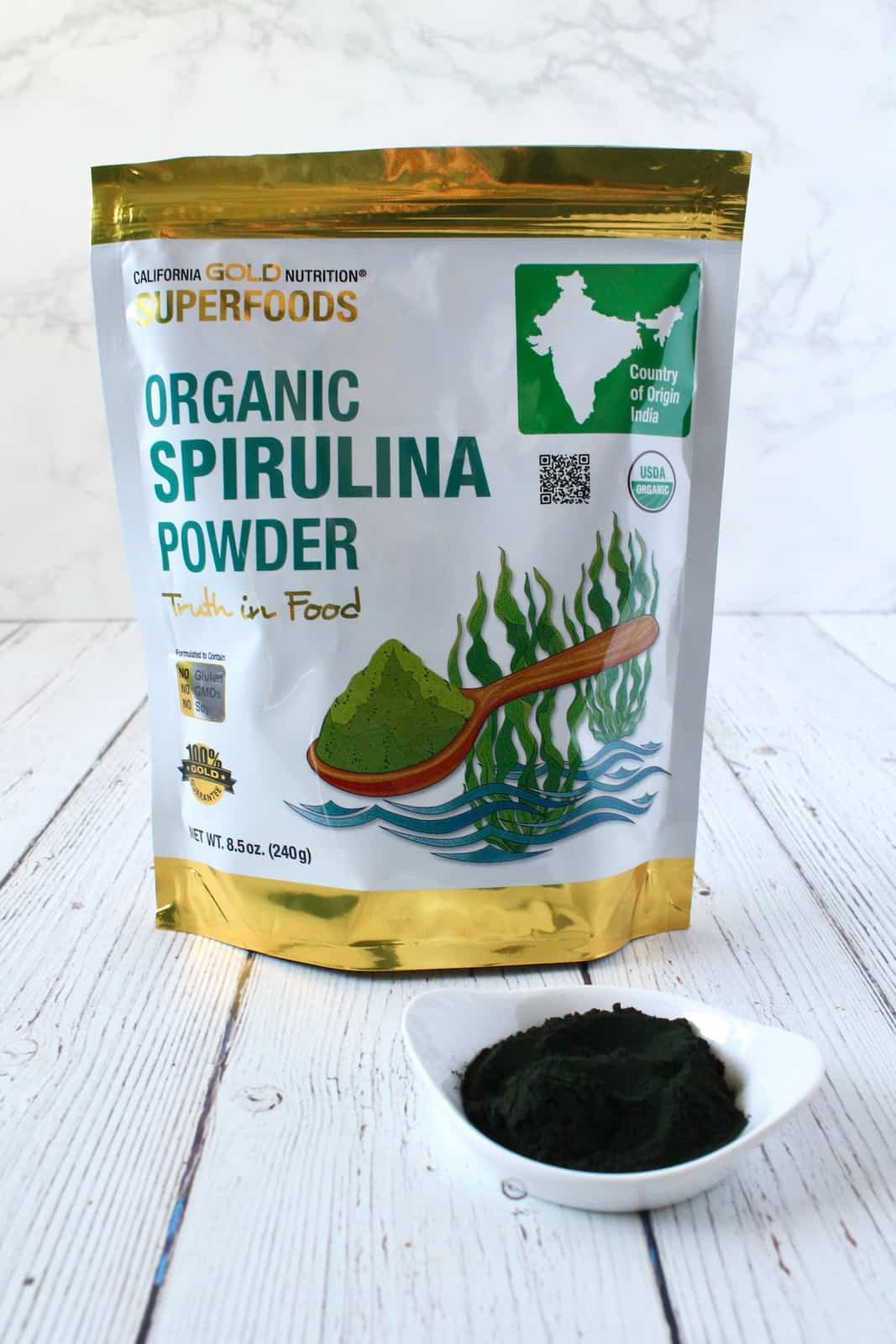 White and gold bag of organic spirulina powder next to a small white dish with dark green powder in it on a white wooden surface with a white marble background