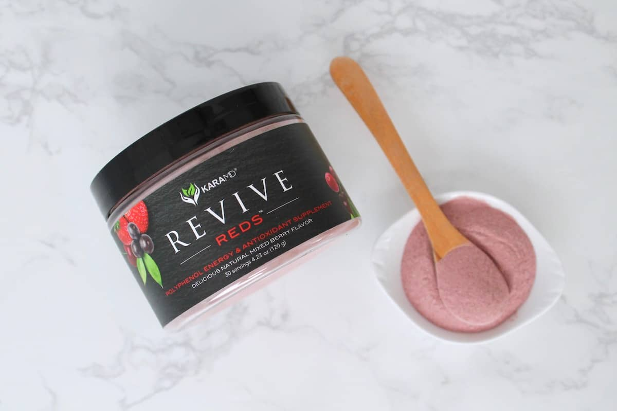 Revive reds supplement powder container on a marble surface next to a small white dish with red powder and wooden spoon in it