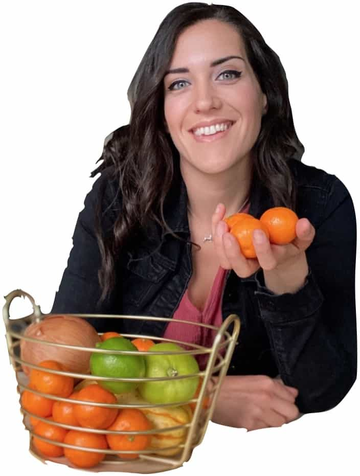 woman with black hair standing over cutting board with vegetables