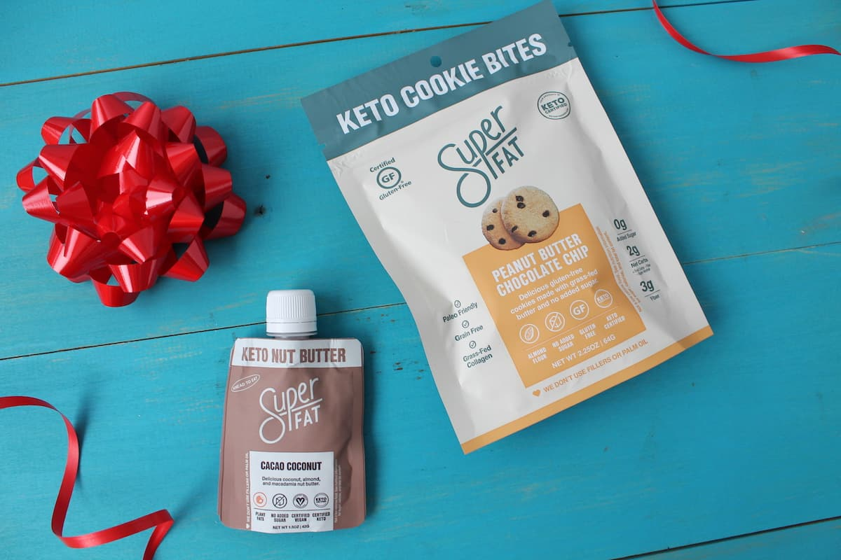 Super fat brand keto snacks on a teal wooden table next to a red bow and red ribbon