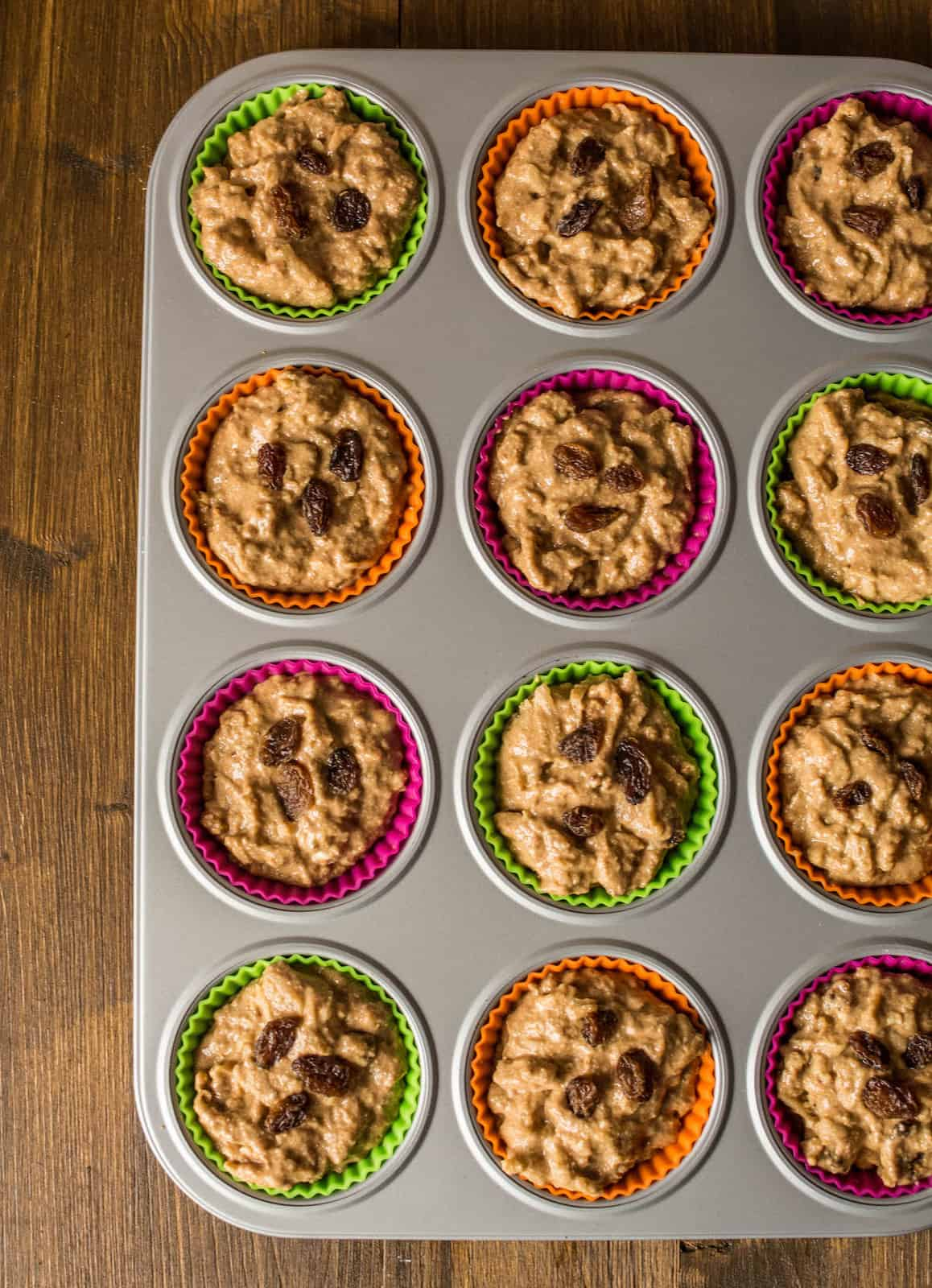 Uncooked apple muffin batter in muffin tin on a brown wooden table
