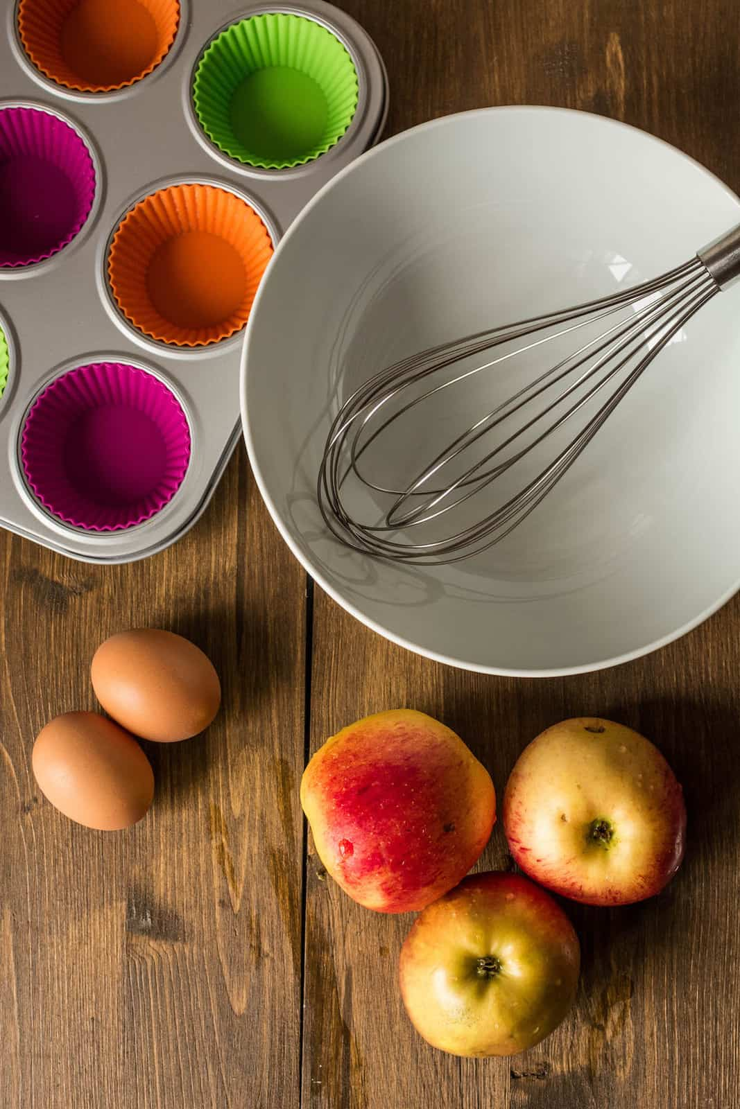 Empty white bowl with whisk in it next to empty muffin tin, apples and eggs on a brown wooden table