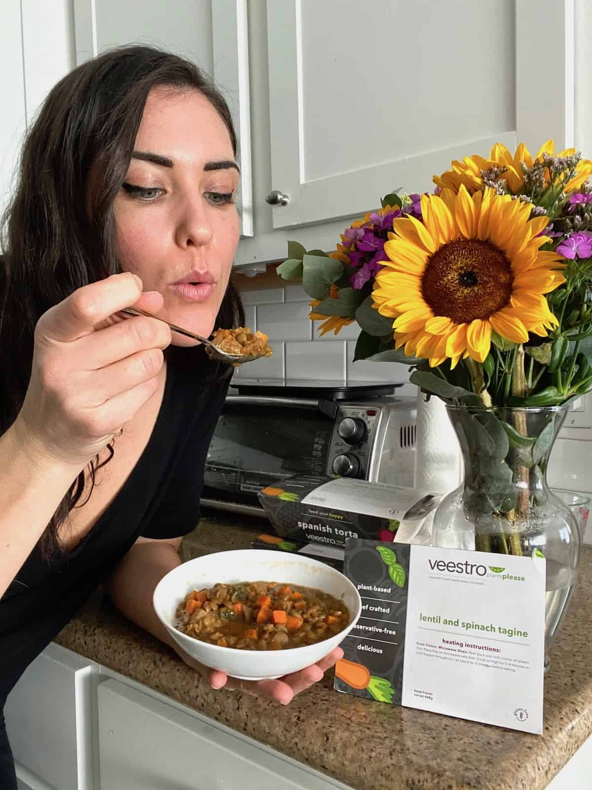 Dark haired woman holding a bowl of lentil tagine next to boxes of veestro meals holding a spoonful of lentils up and blowing on it