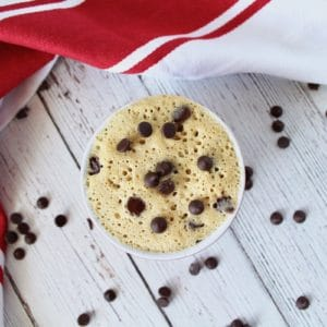 Finished chocolate chip mug cake in a small ramekin on a white wooden surface with chocolate chips surrounding it and a red and white striped dish cloth next to it