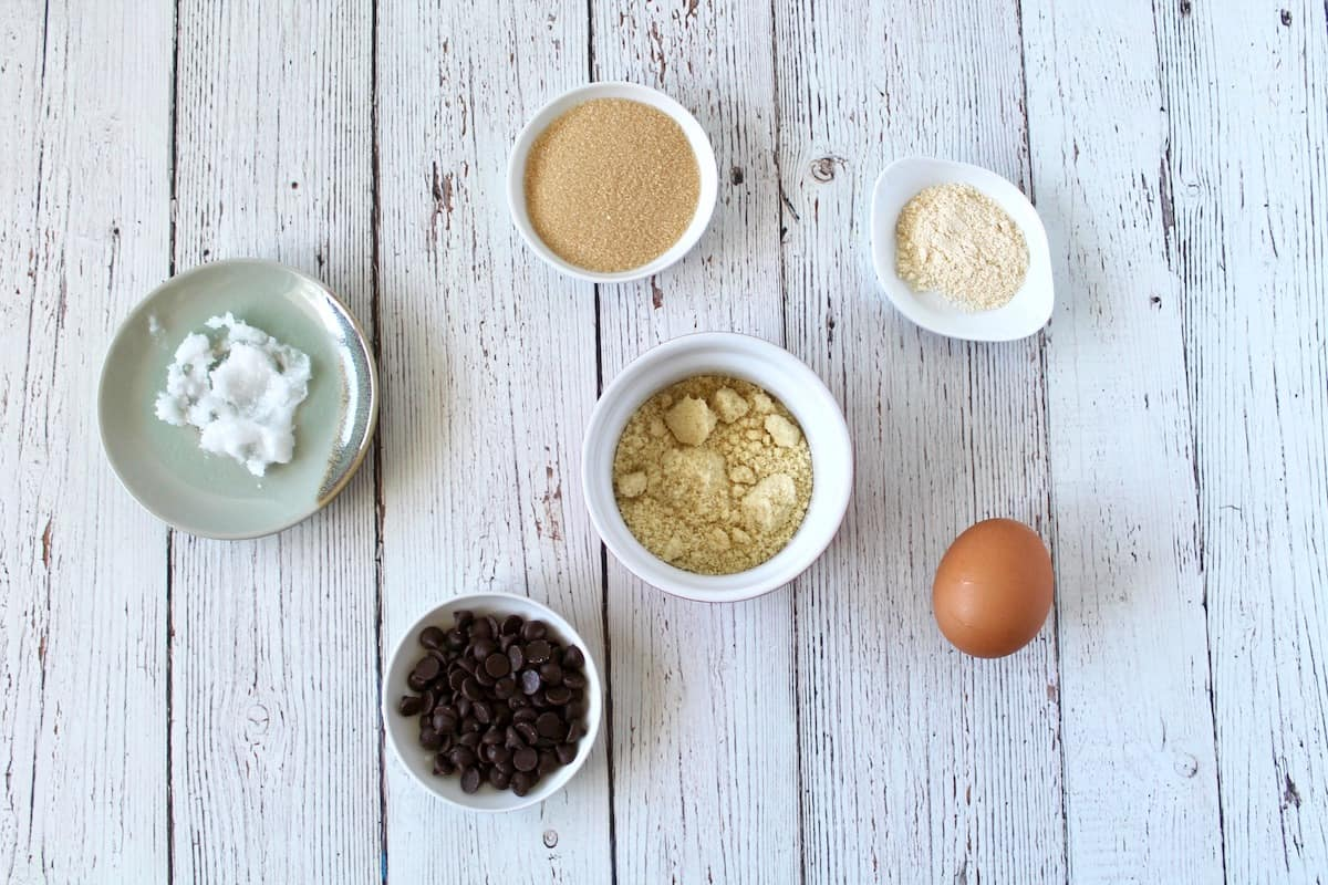 mug cake ingredients laid out in various dishes on a white wooden surface