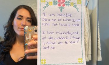 Paper stuck to bathroom mirror with affirmations for self love written on it with woman in the background of the mirror taking picture with phone