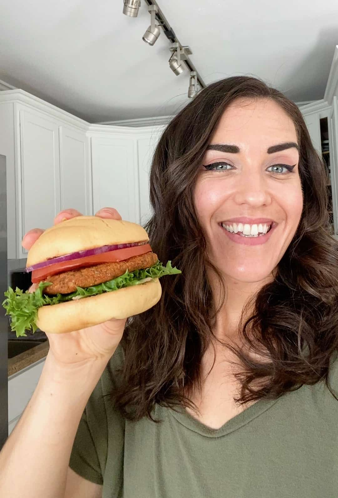 Dark haired woman with green shirt smiling and holding sprouted lentil burger with bun